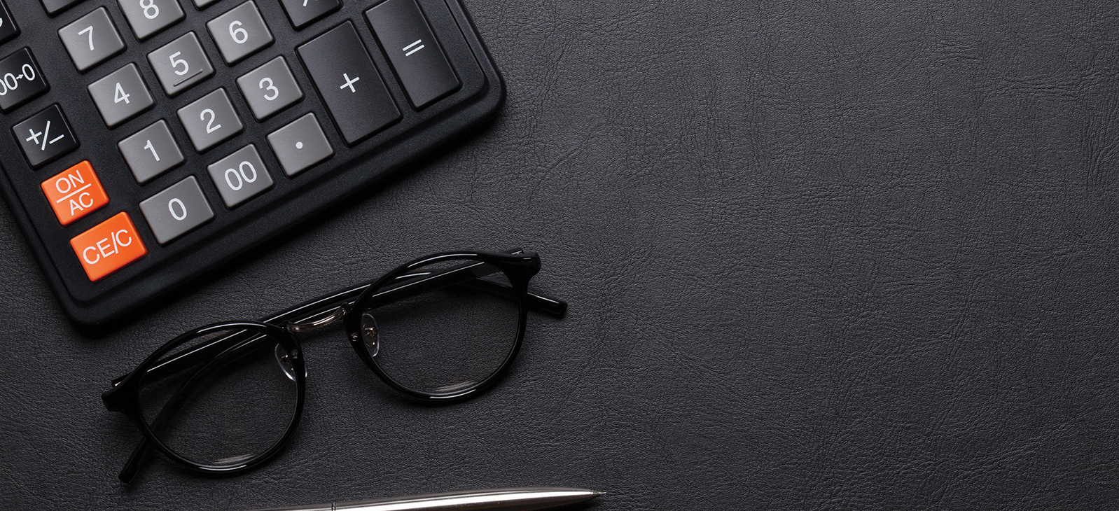 Calculator and glasses with a pen on table