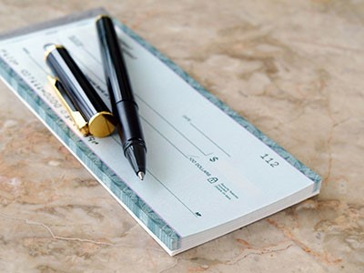 An ink pen resting on top of a check book