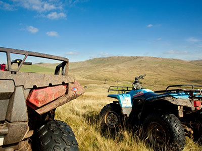 close up of four wheelers parked in a field
